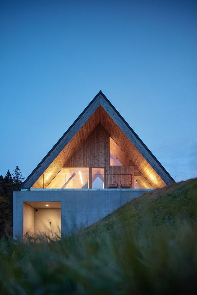 The smooth slope gently wraps around the house, partially enveloping its bottom section