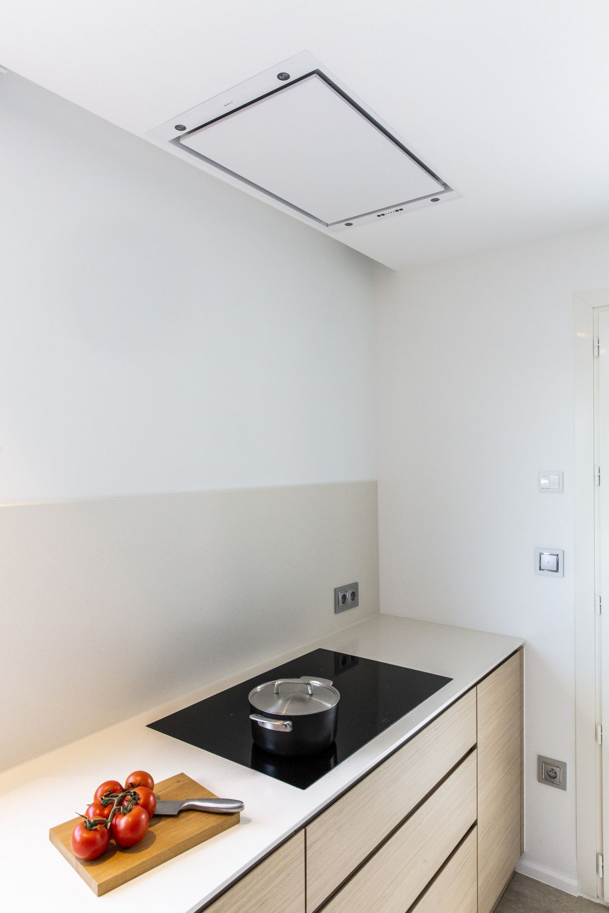 The exhaust hood is neatly incorporated into the ceiling and looks very sleek and simple