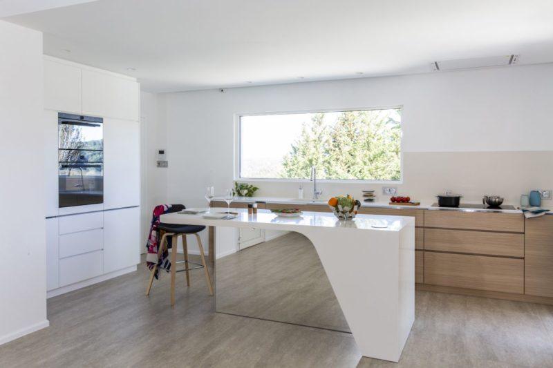 Stylish Kitchen Layout Centered Around A Mirrored Island