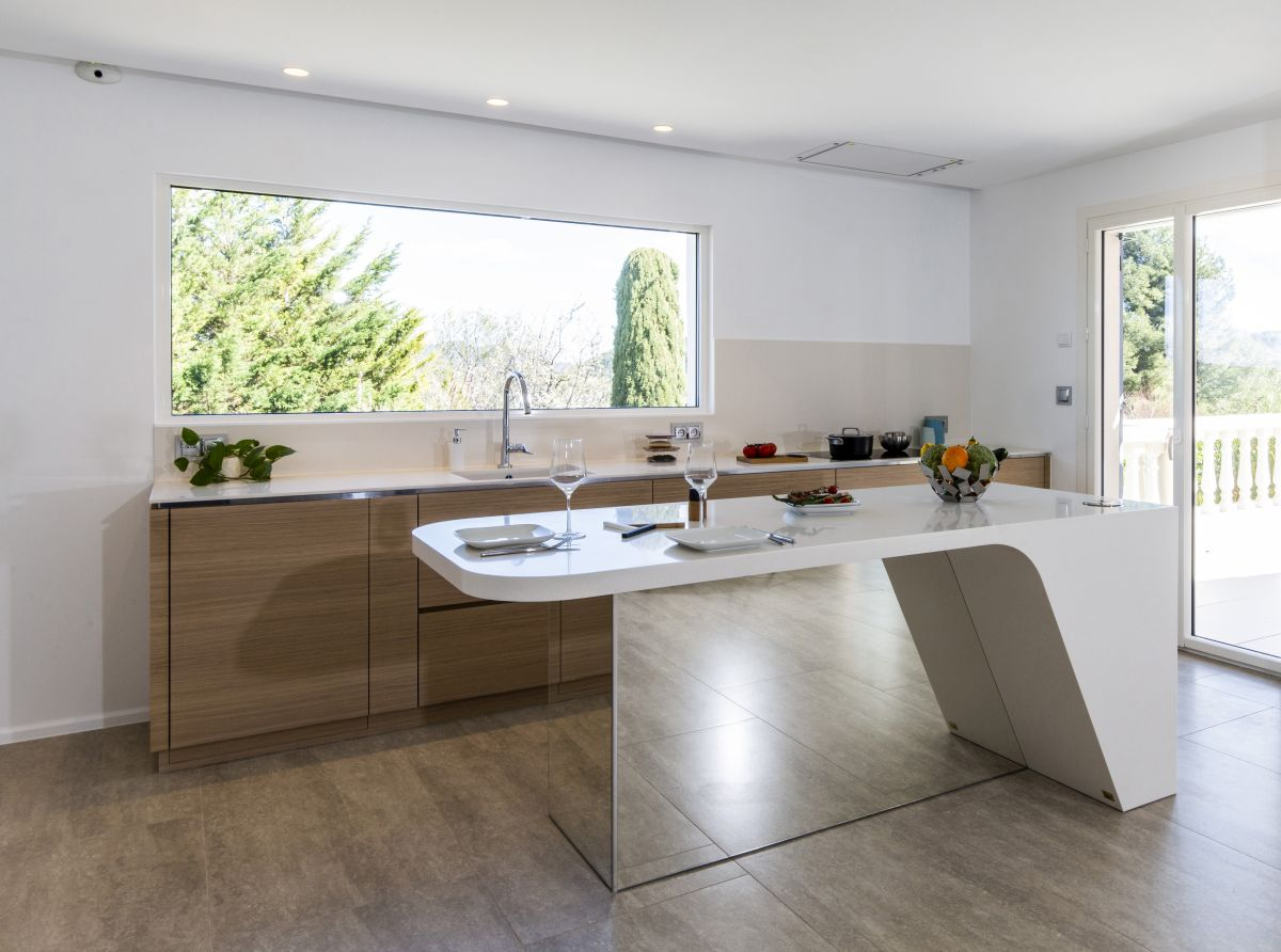 The kitchen looks very warm and welcoming and encourages socialization through its open and modern design