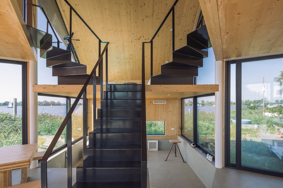 The floors are connected by a metal staircase which splits into two sections