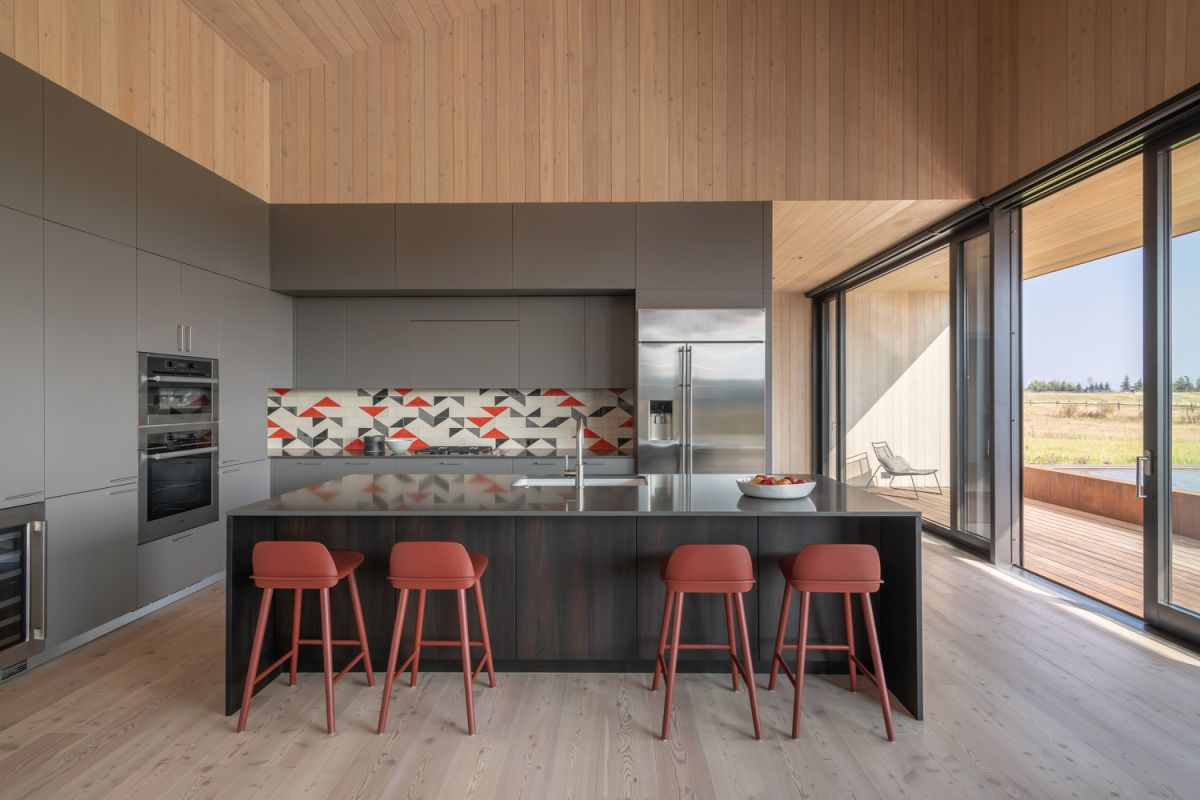 The kitchen is part of a large common area with sliding glass doors that connect it to a terrace
