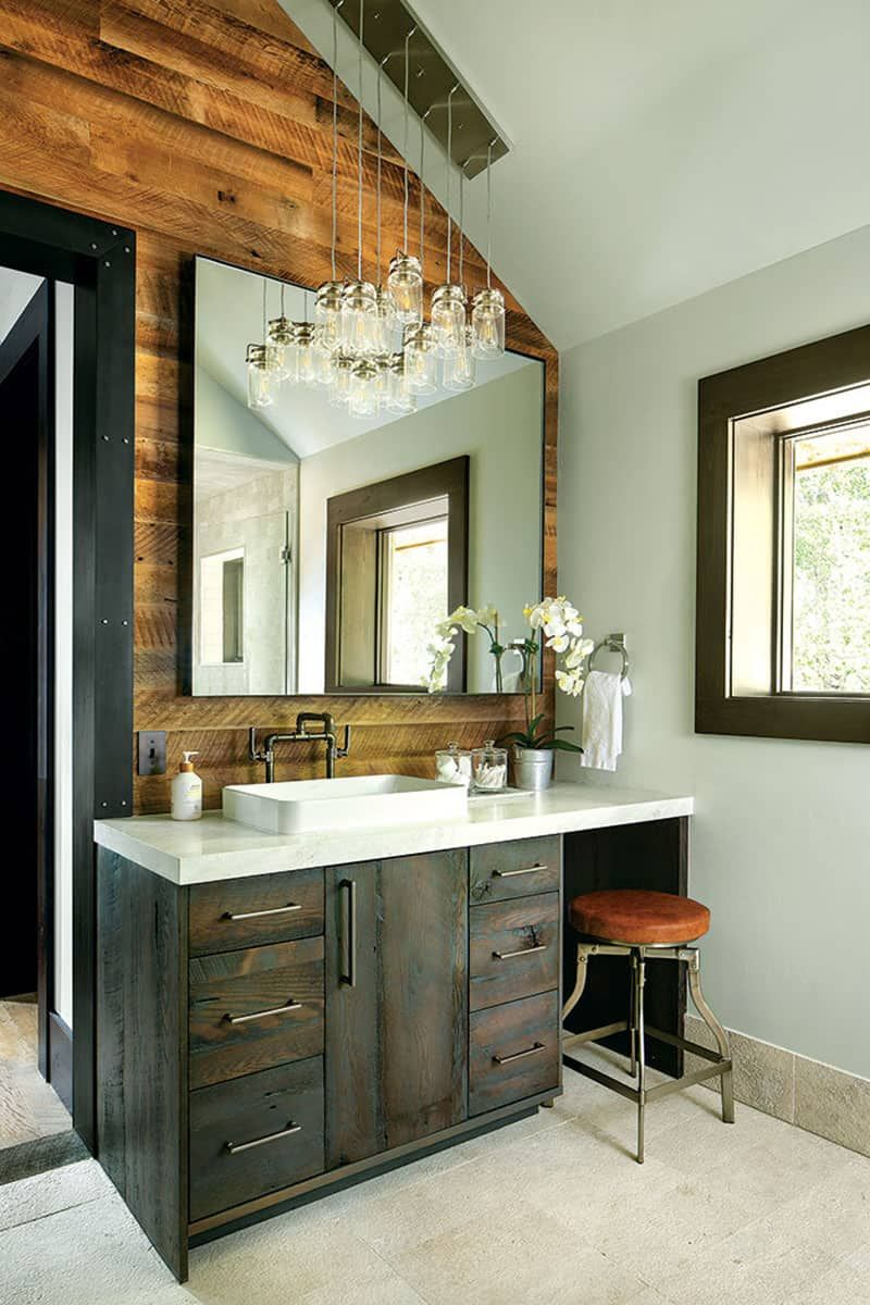 This section of the bathroom maximizes the natural and artificial light through a large wall-mounted mirror