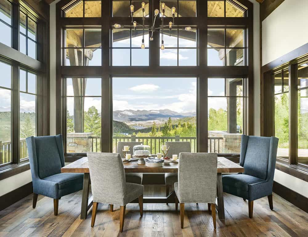 The dining area is framed by large windows on three sides and has a magnificent view of the mountains