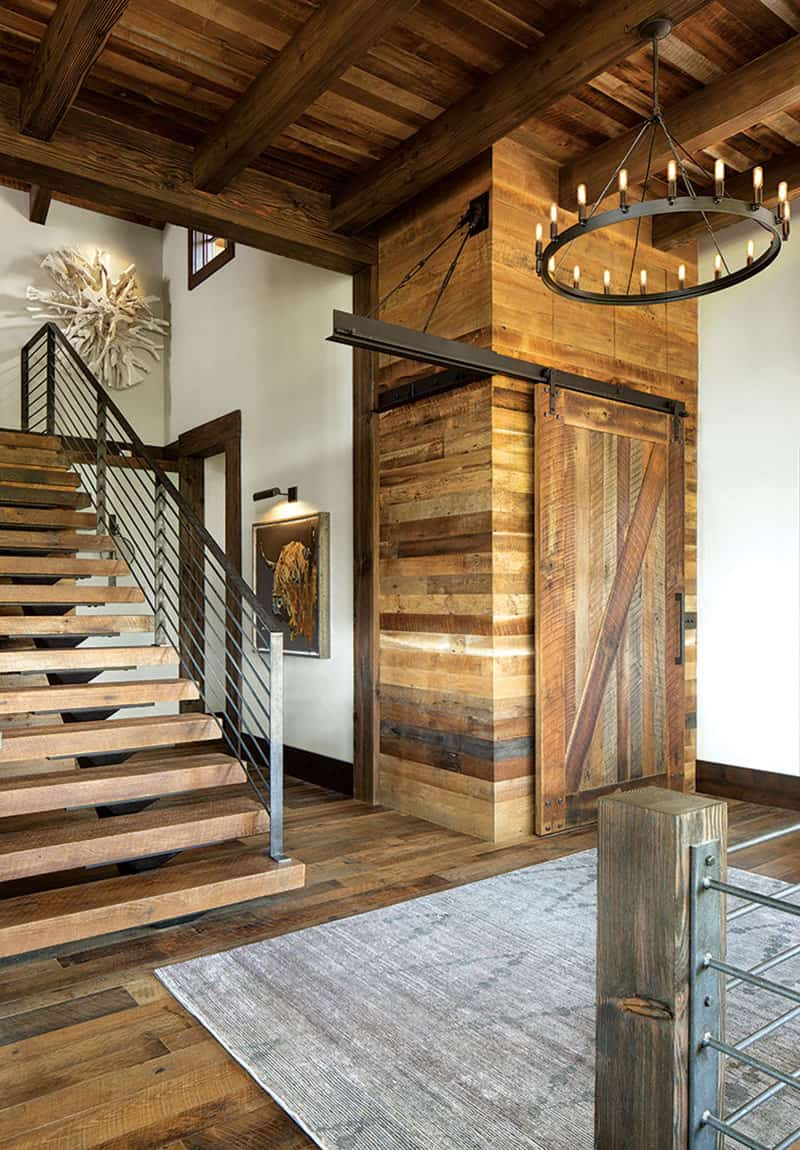 The house follows a rustic aesthetic with farmhouse influences, as shown by features such as this barn door