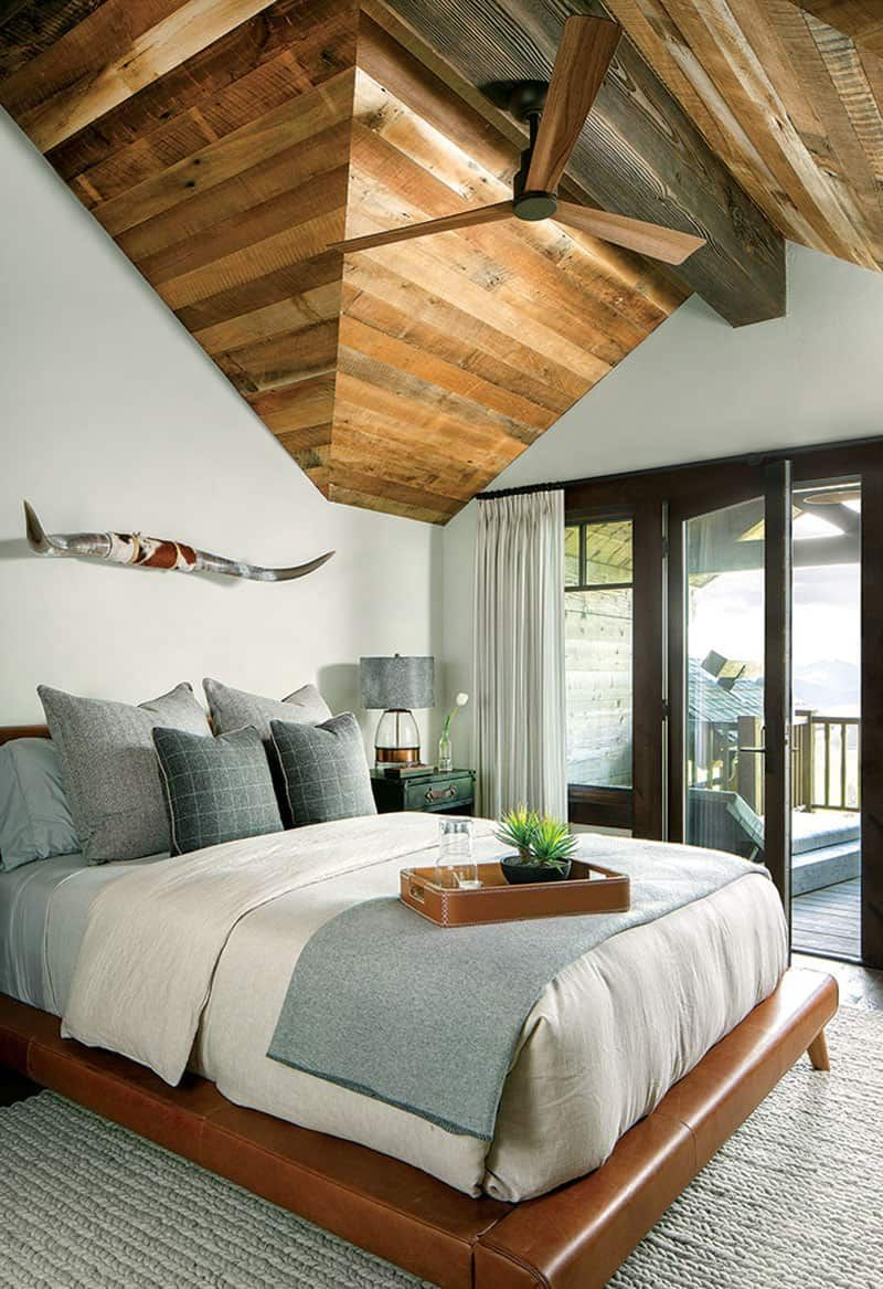 The white walls of this bedroom complement the wooden ceiling in a really nice way, ensuring a bright and open decor