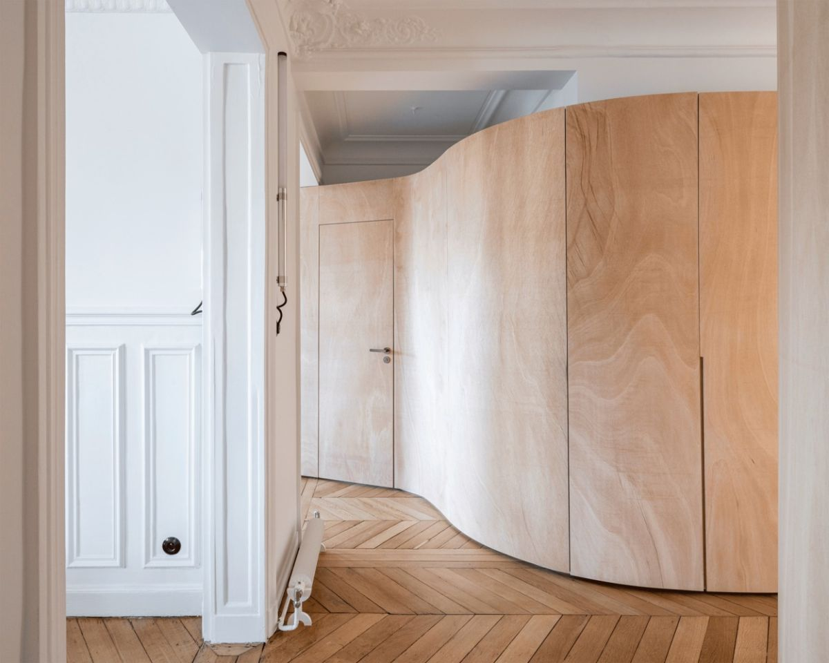 The undulating wooden wall has become the new partition between the major sections of the apartment