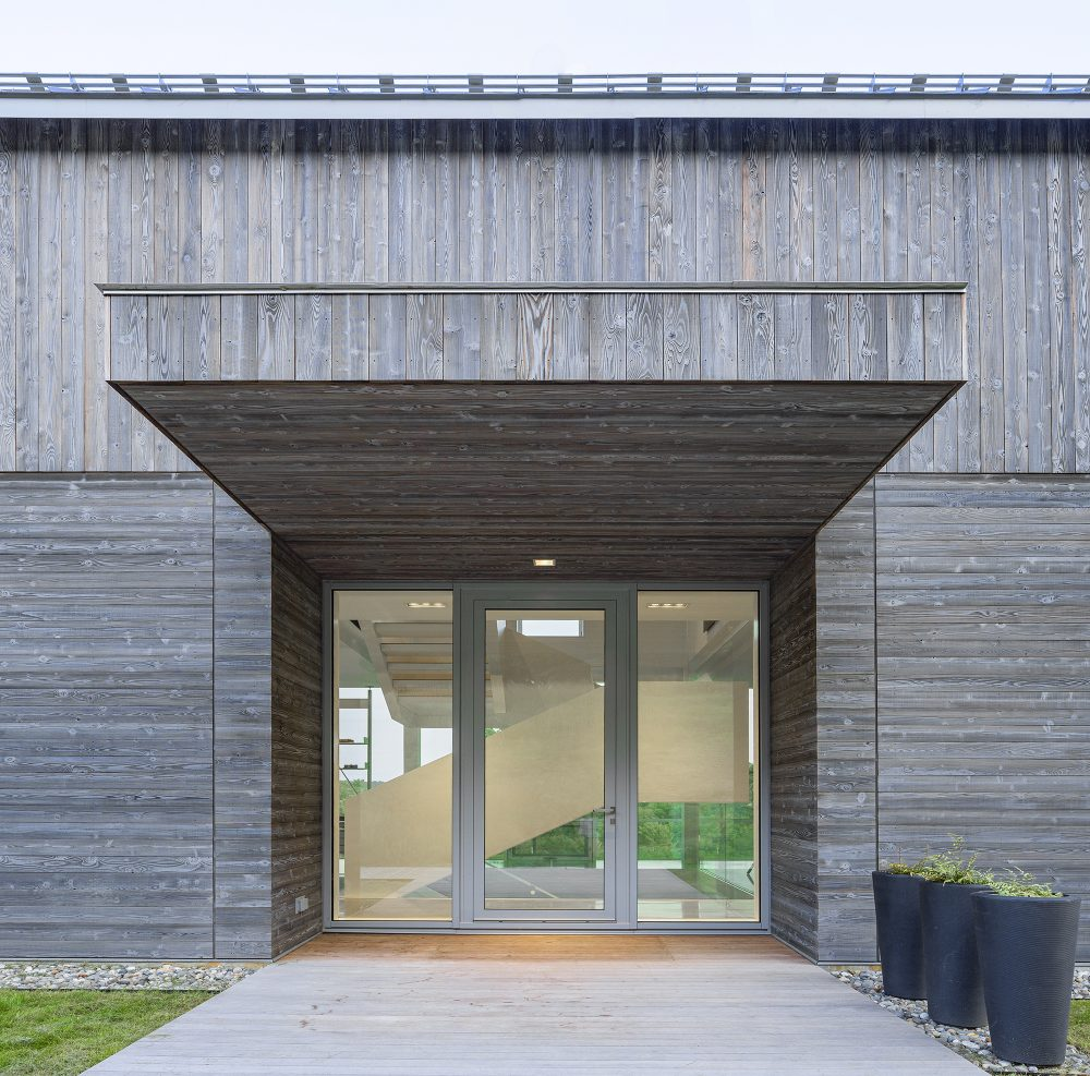 The entrance offers a peak inside the house and is sheltered by a wooden overhang