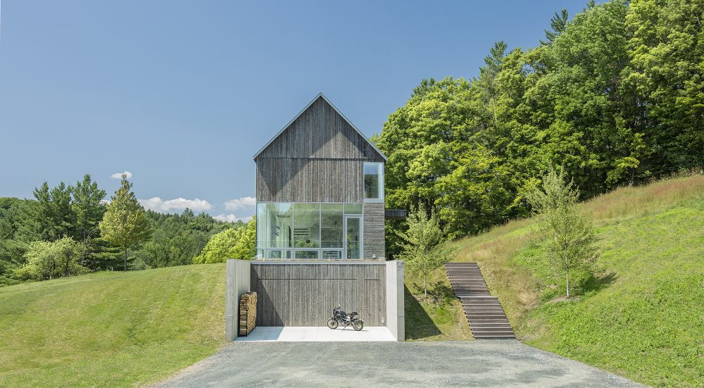 The house is three levels tall with the lowest one being integrated into the hillside