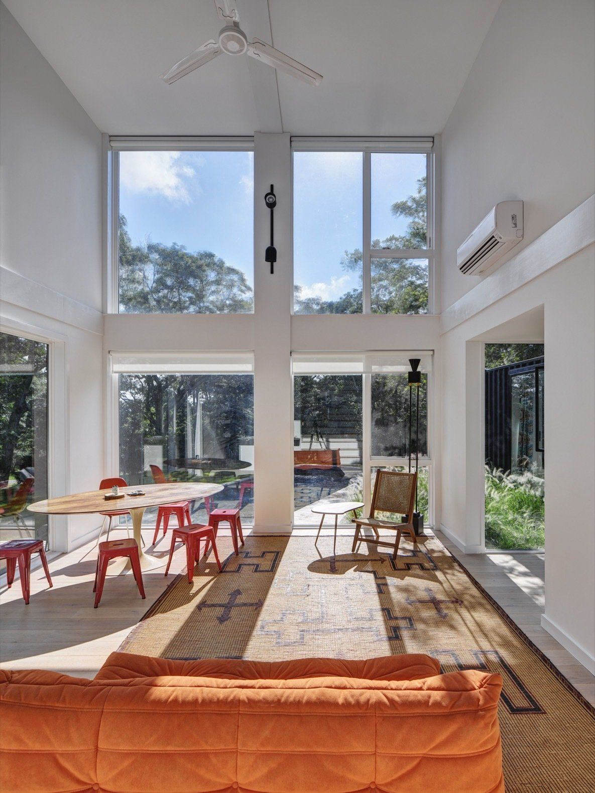 The living area is a double-height space with glass doors and windows and a simple and cozy decor