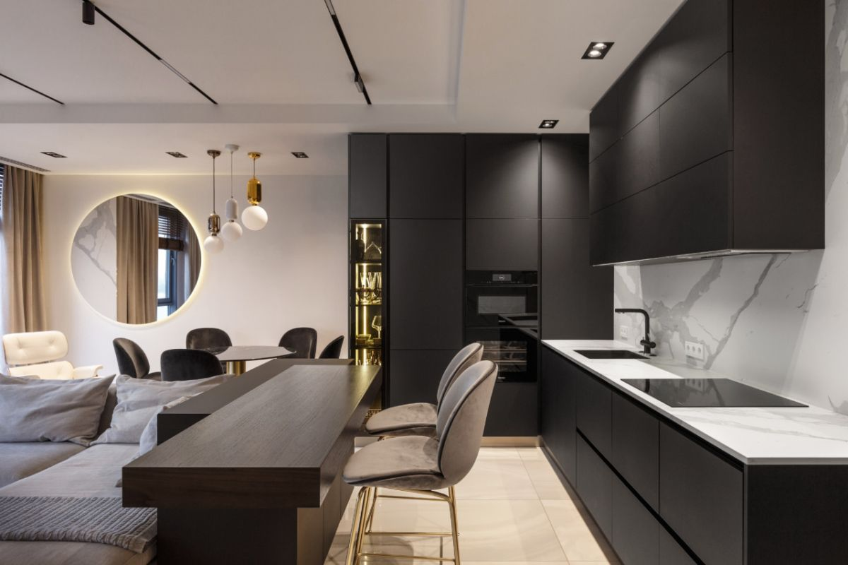 The kitchen has all black cabinetry complemented by white marble countertop and backsplash surfaces