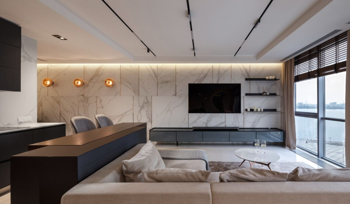 There's an entire wall in the living room covered in stylish white marble tiles
