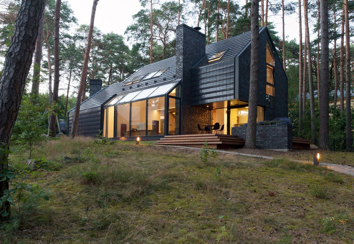 This black house is nestled in the forest and takes full advantage of its remote location