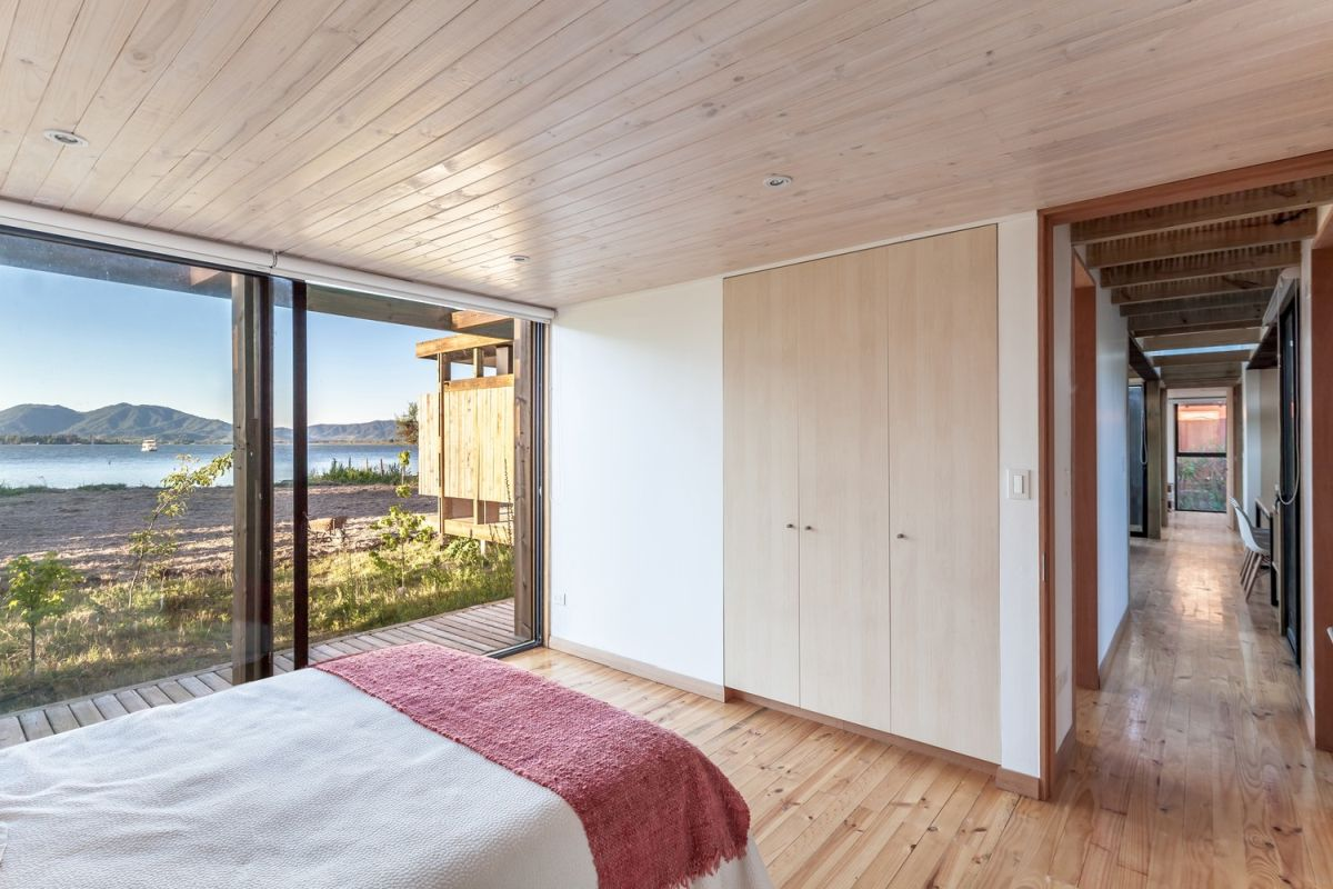 Large full-height windows frame views of the lake and expose the interior spaces to the beautiful outdoor surroundings