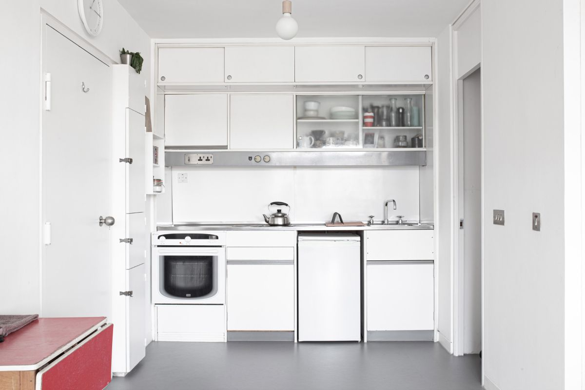The kitchen is compact and white which helps to give it a bright and airy look