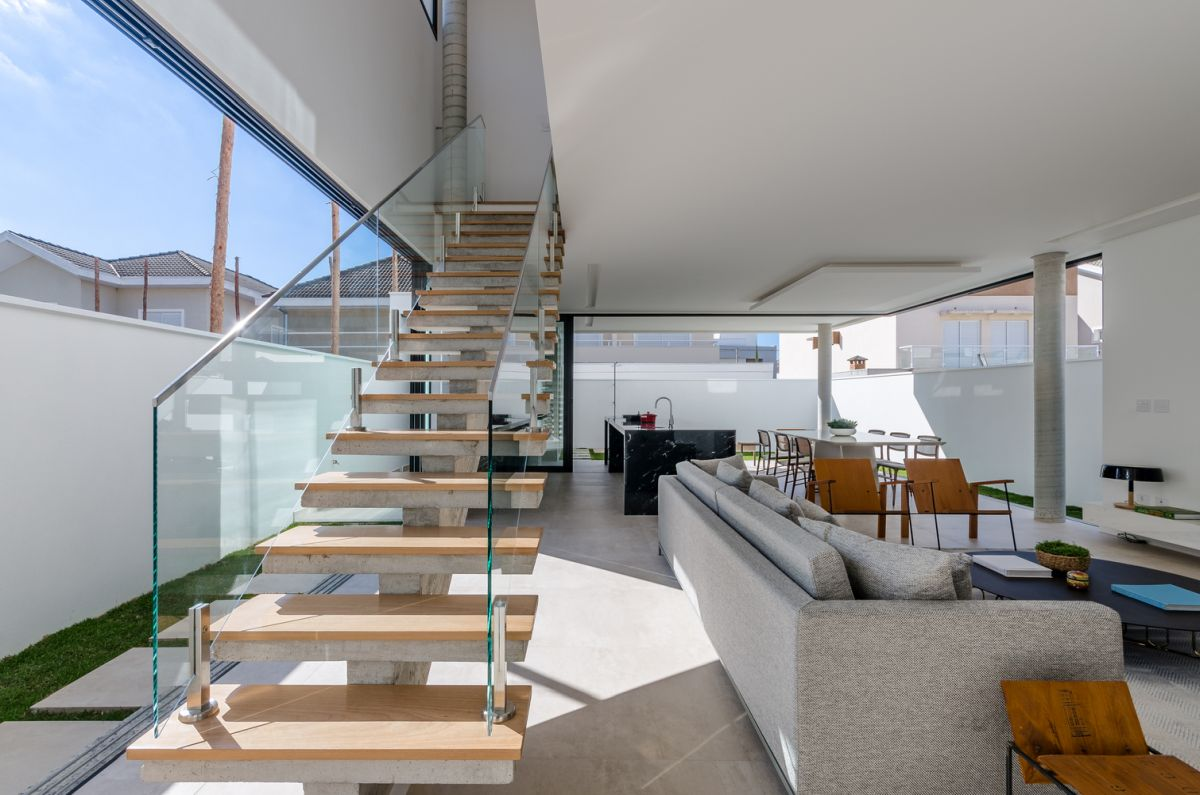 The ground floor social area and the upstairs bedrooms are connected by a staircase with transparent glass balustrades