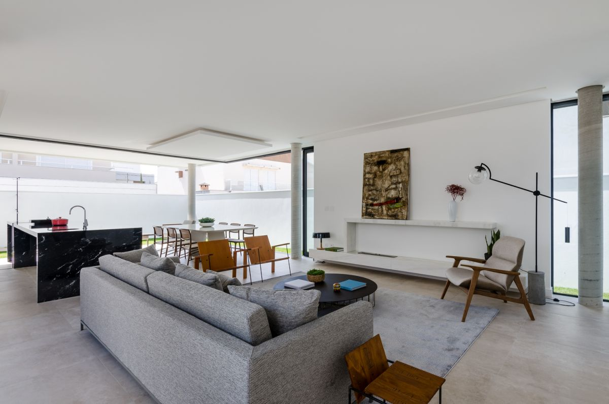 The living area is placed at the center of the room, framed by a light gray area rug