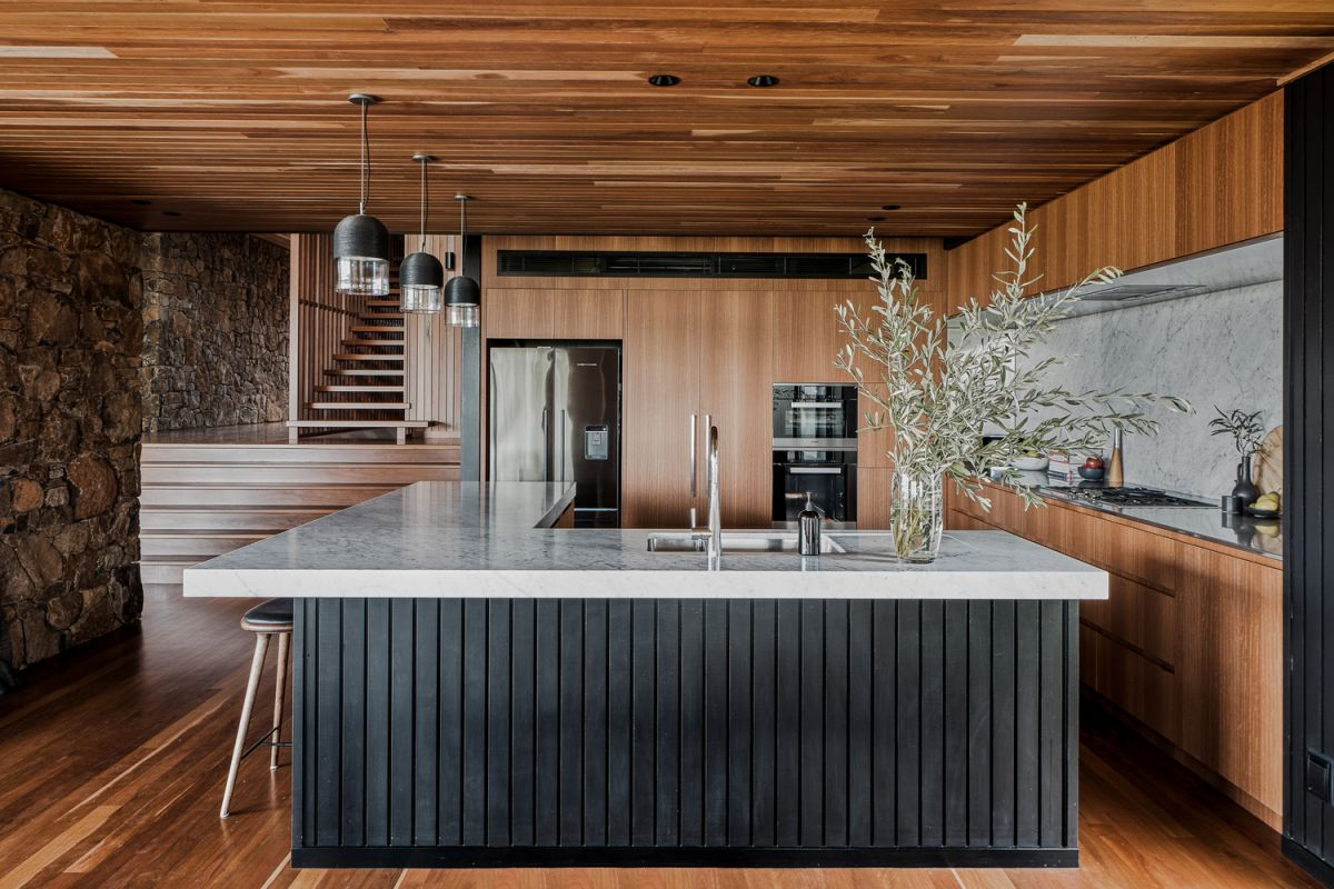 The kitchen is positioned in one of the corners and has a large L-shaped counter which doubles as a divider