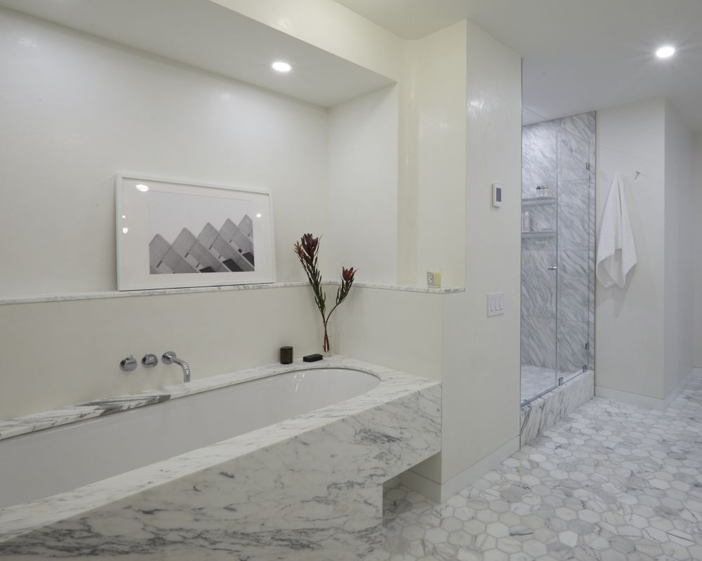 White marble adds lots of elegance to the master bathroom and complements its minimalistic style