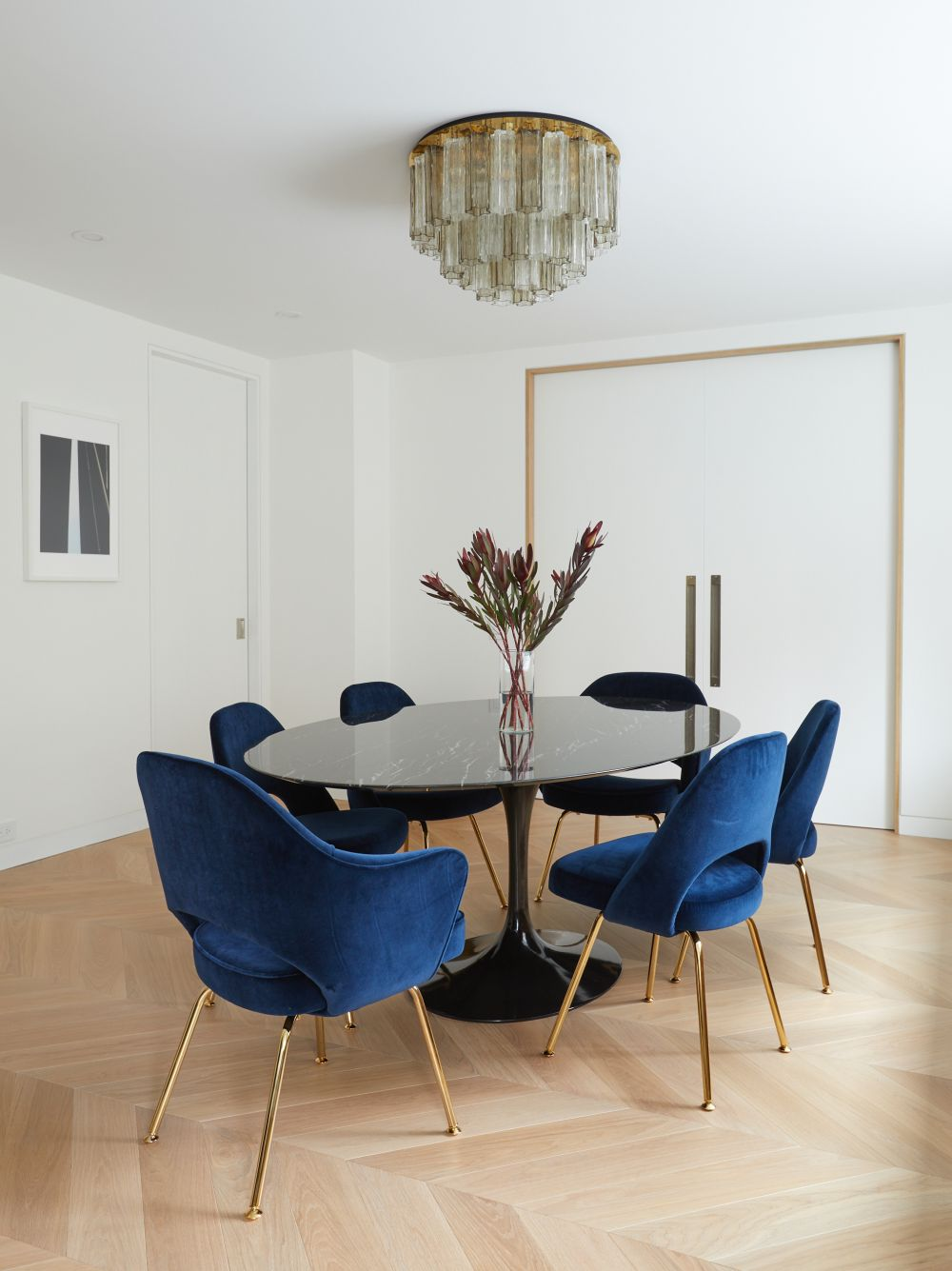 The dining area is furnished with a gorgeous black table with a lacquered finish and stylish blue chairs