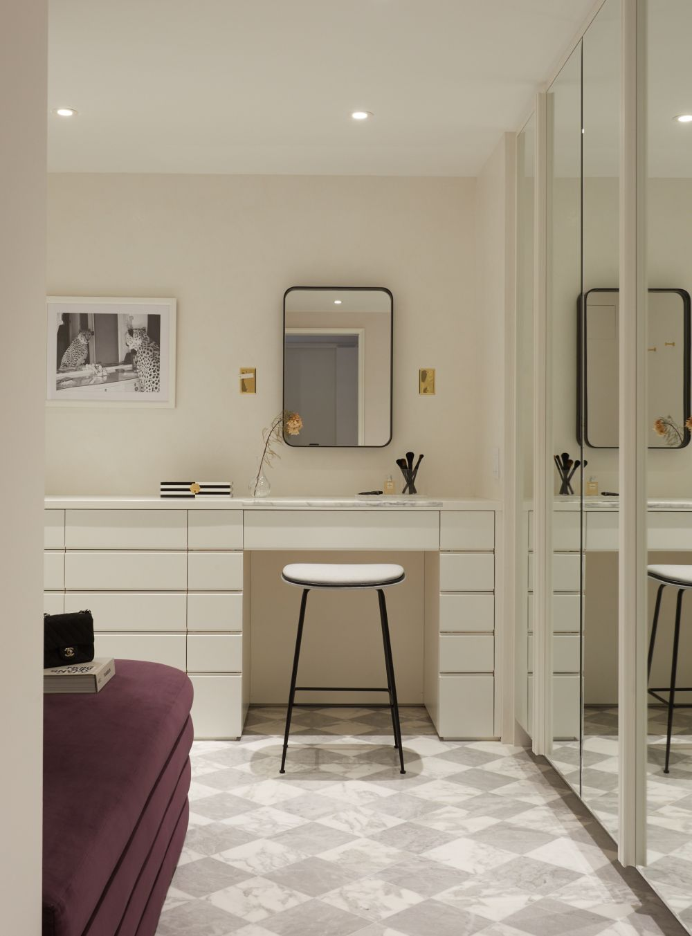 This room also has a custom vanity complemented by a stylish mirror and a sleek accent chair