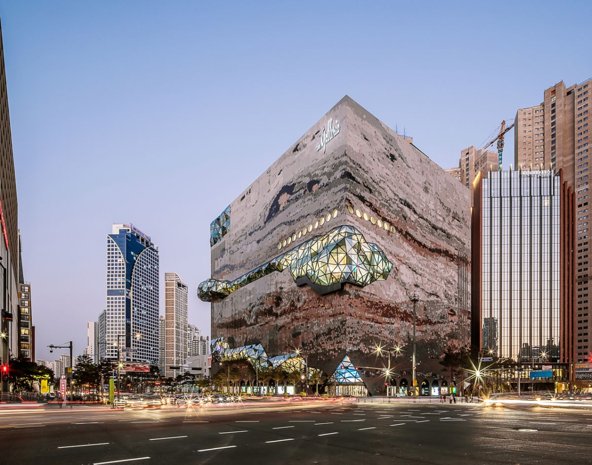 The contrast between the glass and the stone surfaces highlights the unusual and unique design of the building