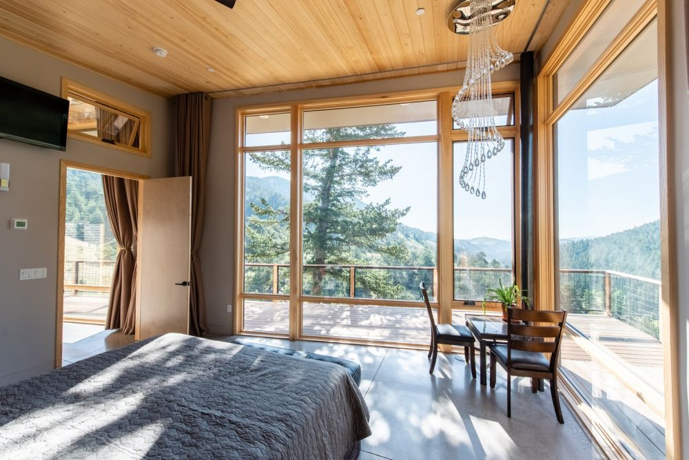 This stylish bedroom opens onto a deck that wraps around the corner to maximize the gorgeous views