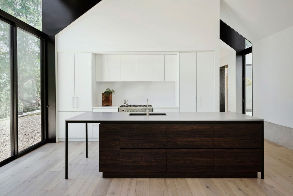 The kitchen is entirely white with the exception of the island which has a dark timber finish