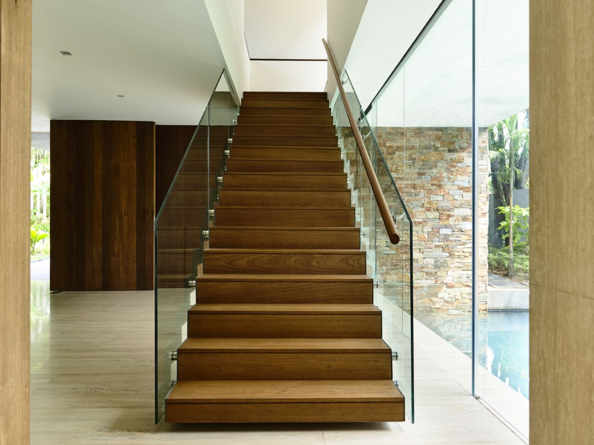 The staircase is placed parallel to a glass wall framing a splendid view of the backyard areas