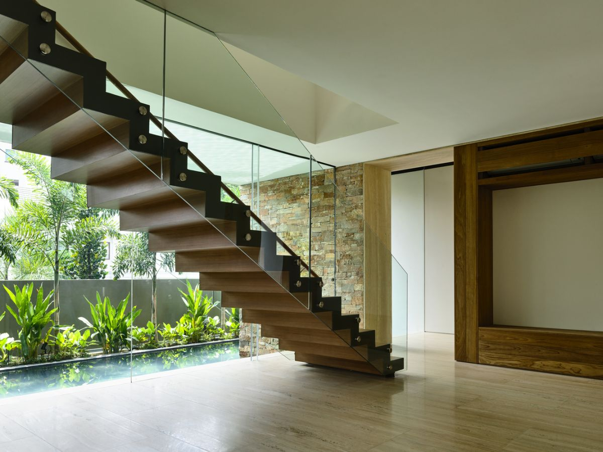 A sculptural staircase with transparent glass guardrails connects the floors