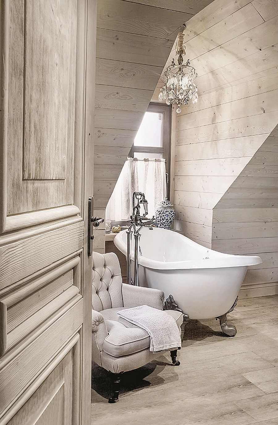 In the bathroom, a gorgeous clawfoot tub is placed in a window nook, complemented by a crystal chandelier