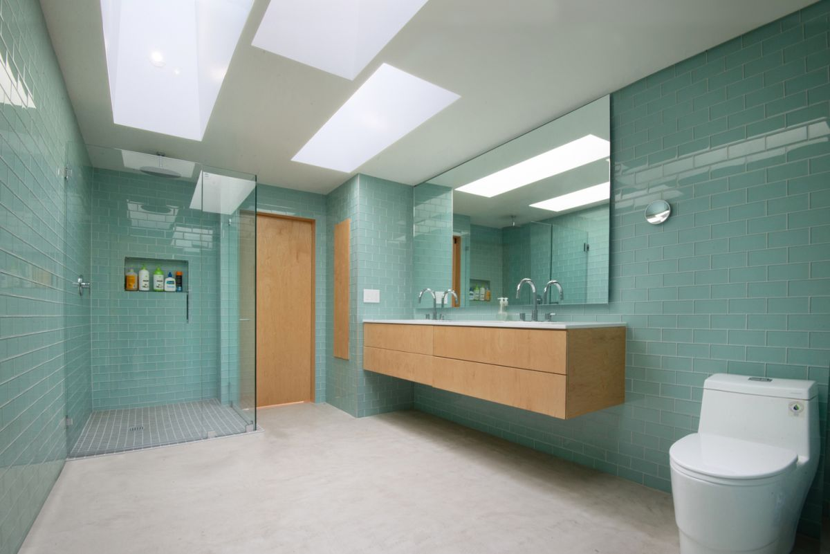 The bathroom has skylights and turquoise wall tiles