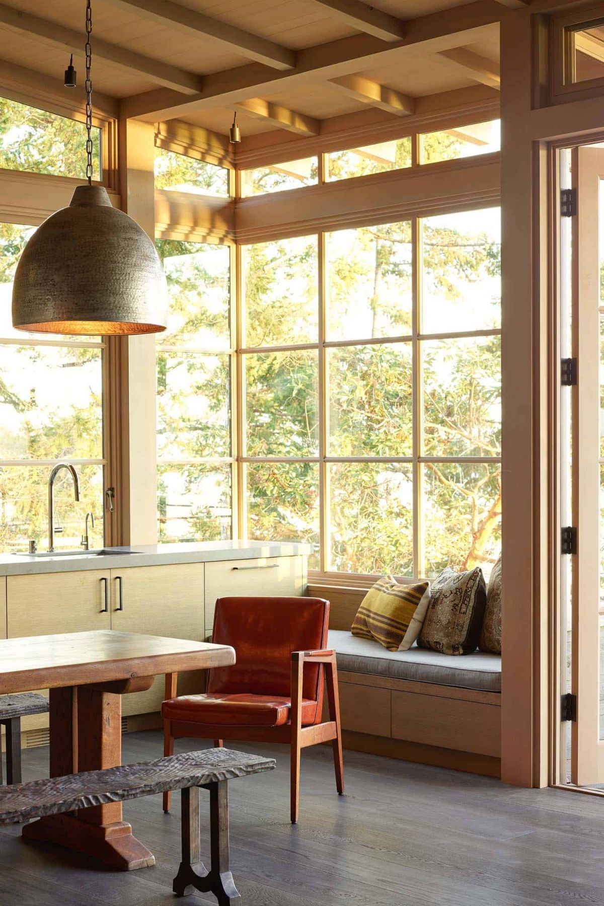 The kitchen has an open concept design and includes a cozy seating nook by the window