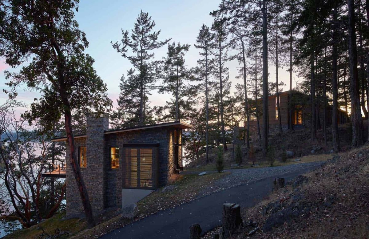 The two small houses are surrounded by tall trees which have been carefully preserved
