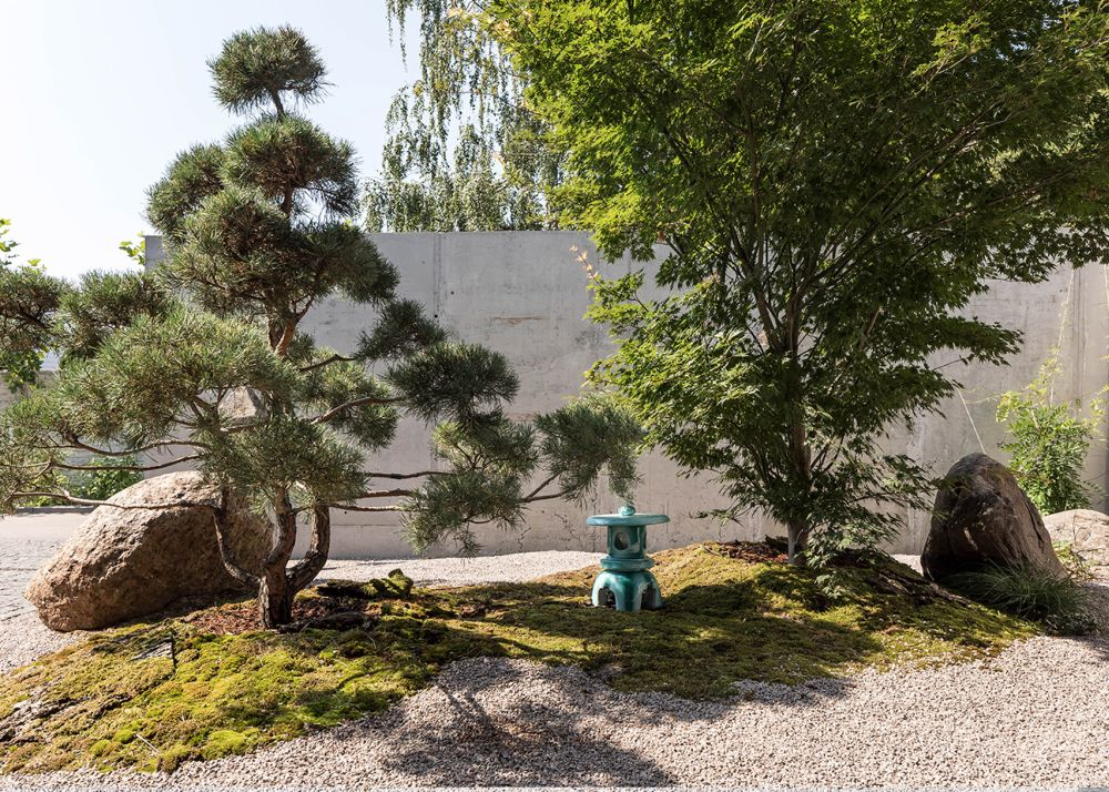 The garden is landscaped and decorated with various sculptures and vegetation that reference the Asian culture
