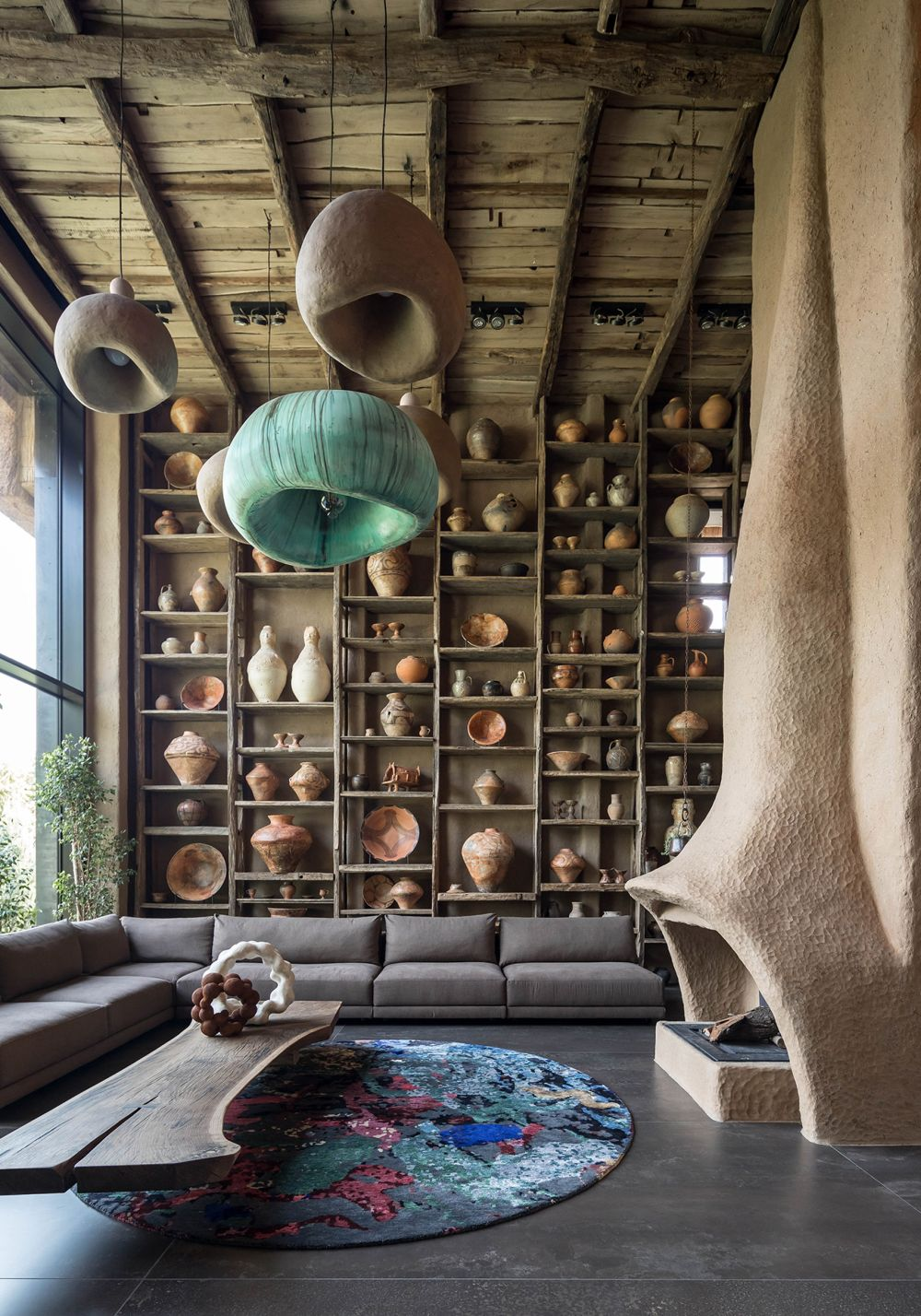 The living room is a double-height space with a very organic decor