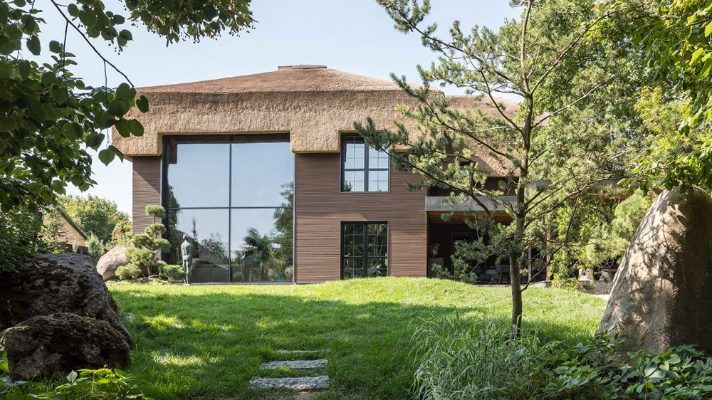 The house has a thatched roof which adds a beautiful texture to its design