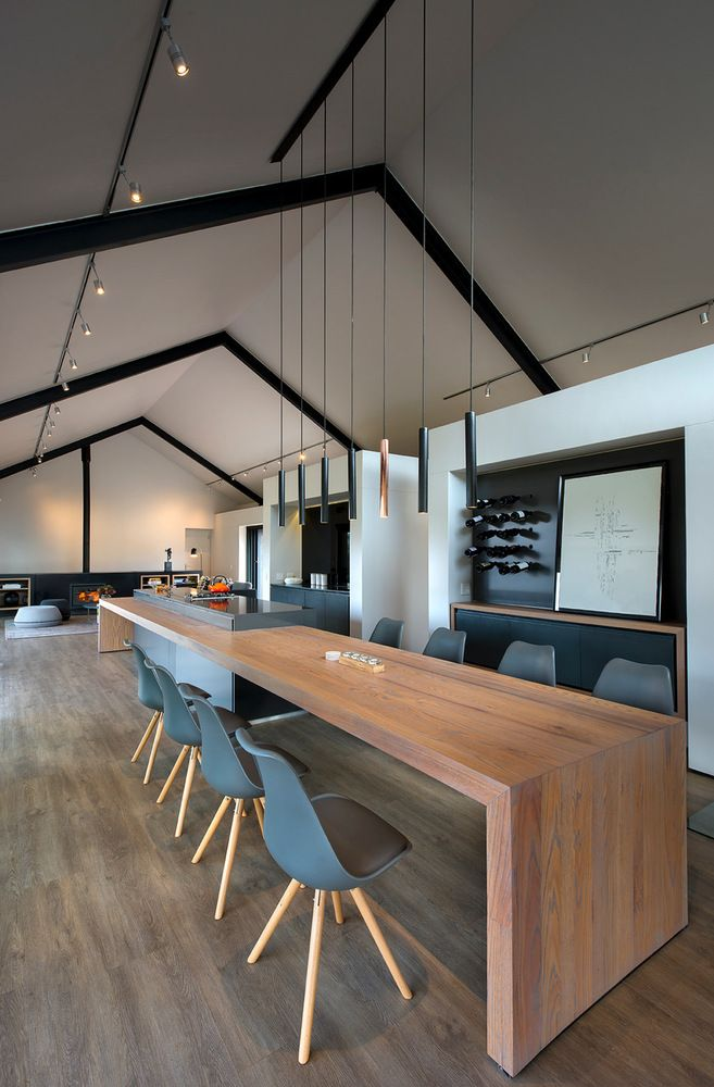 The kitchen island is extra long and transitions into a bar and dining table
