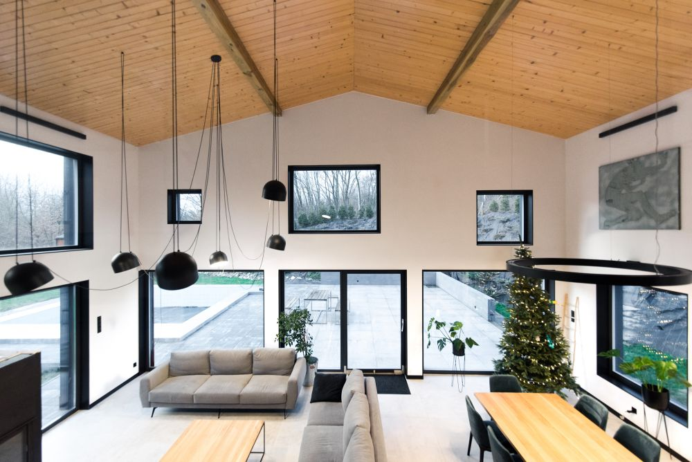The double-height living area is framed by lots of irregular windows which bring in sunlight and beautiful views