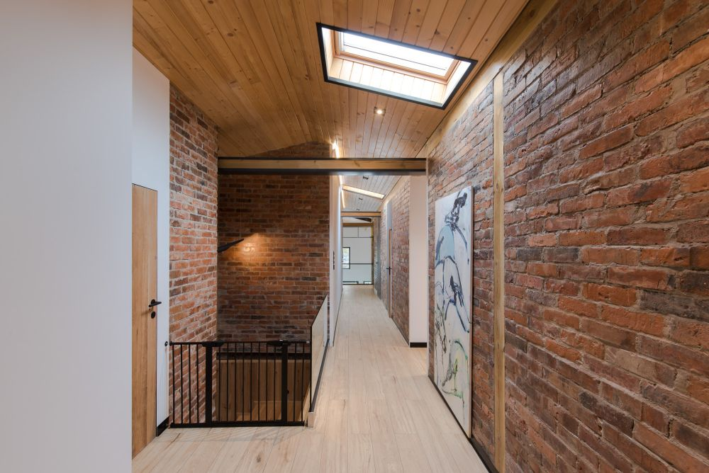 The preserved brick surfaces go really well with the wood accents and add warmth and texture to the design