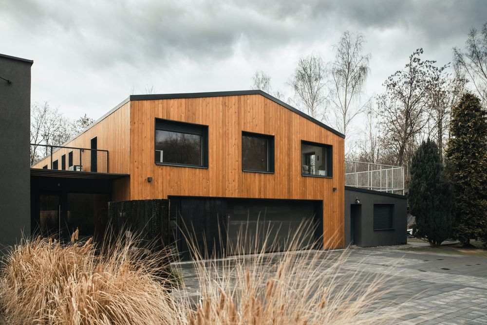 The exterior of the house is clad in wood with black contrasting outlines around the openings