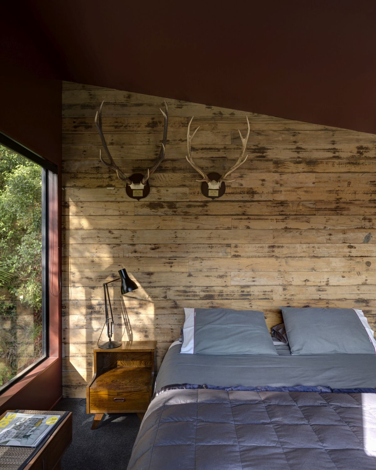 The wood-paneled bedroom wall and angled ceiling add warmth and character to the space