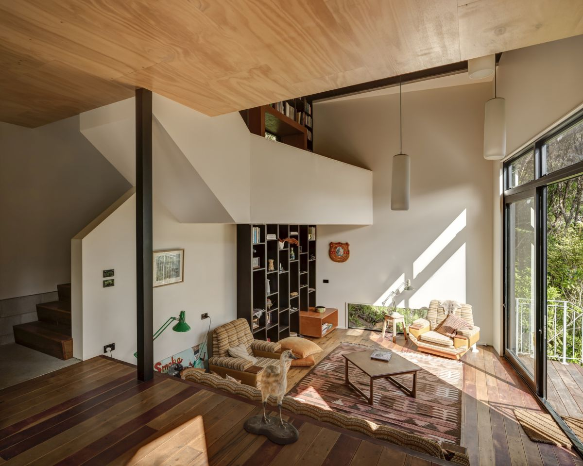 The wooden floor and ceiling add symmetry to the interior design and complement the plain white walls
