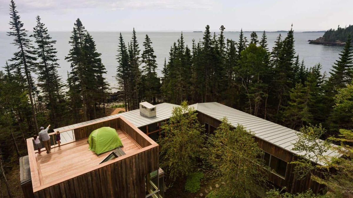 Gaps between the tall trees allow the cabin to enjoy a view of the ocean