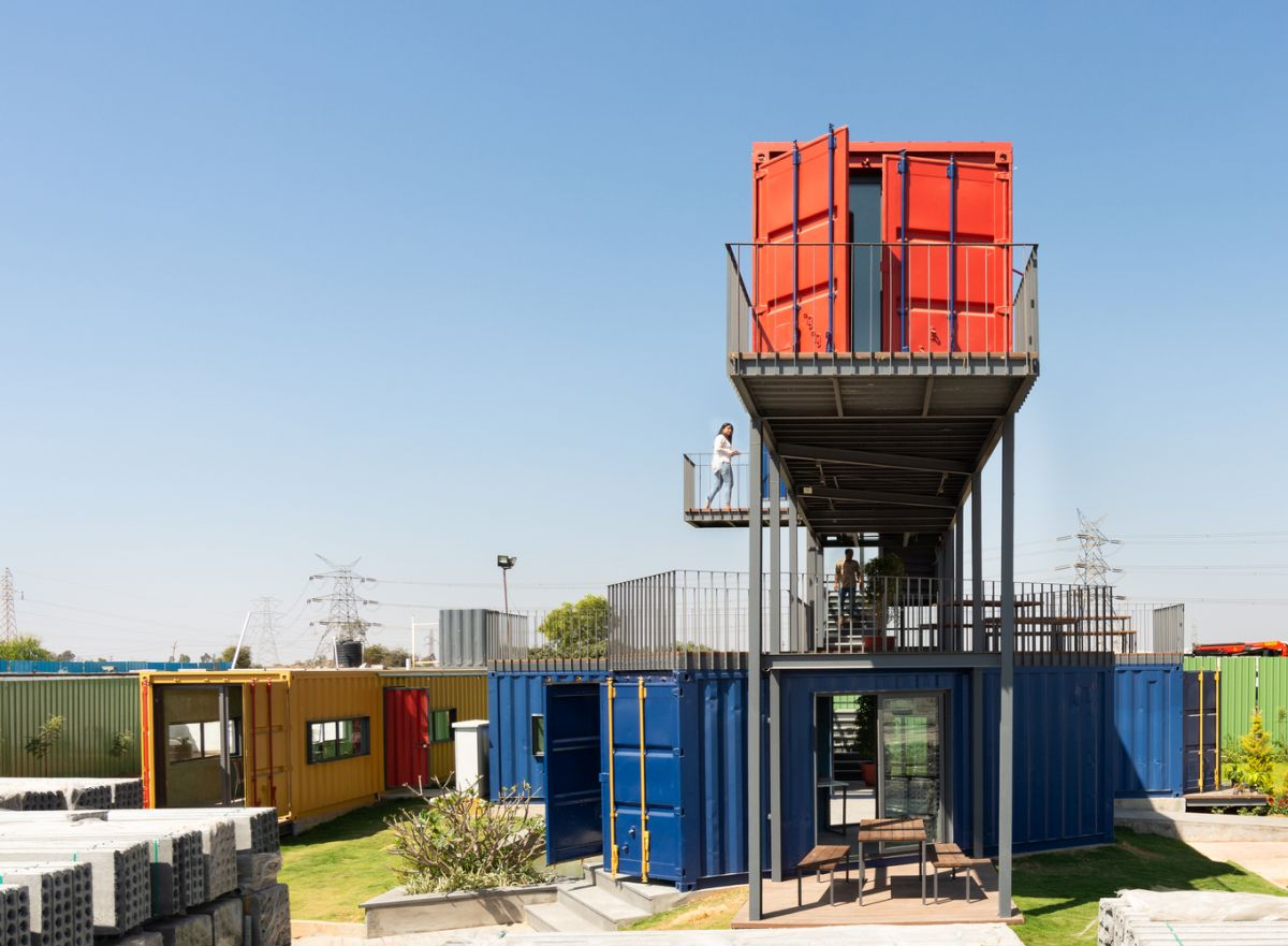 The red container is elevated high above the ground and can be accessed via a cantilevered staircase