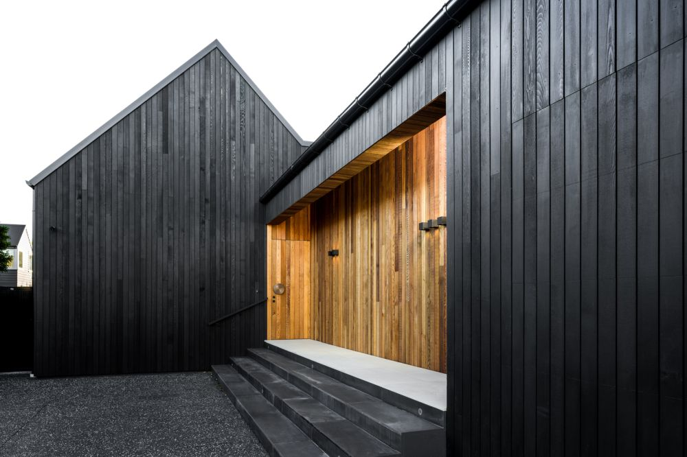 The entrance is defined by the use of natural cedar which contrasts with the black exterior walls