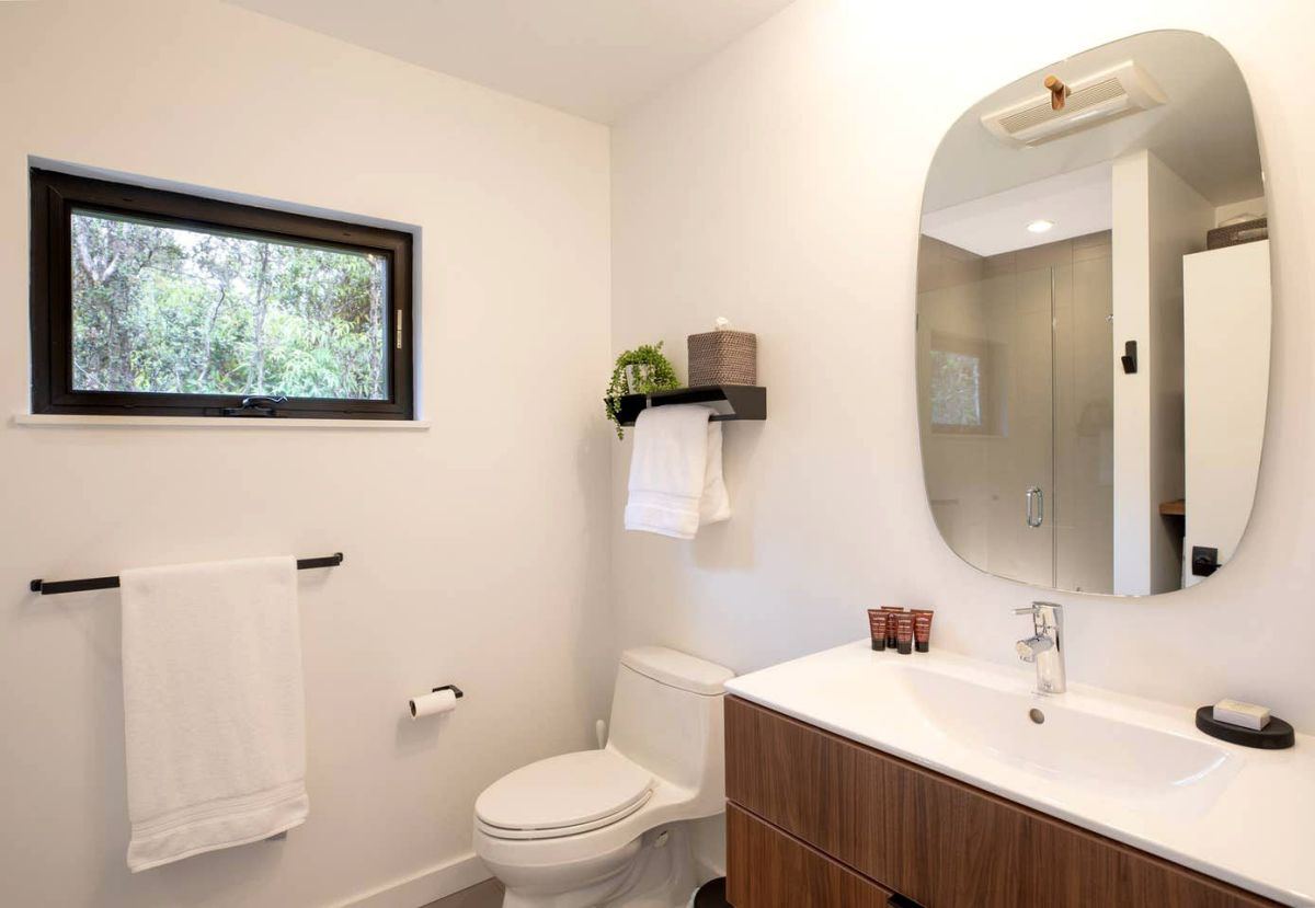 The bathroom is bright and airy, with adequate lighting, a small window for ventilation and white amenities