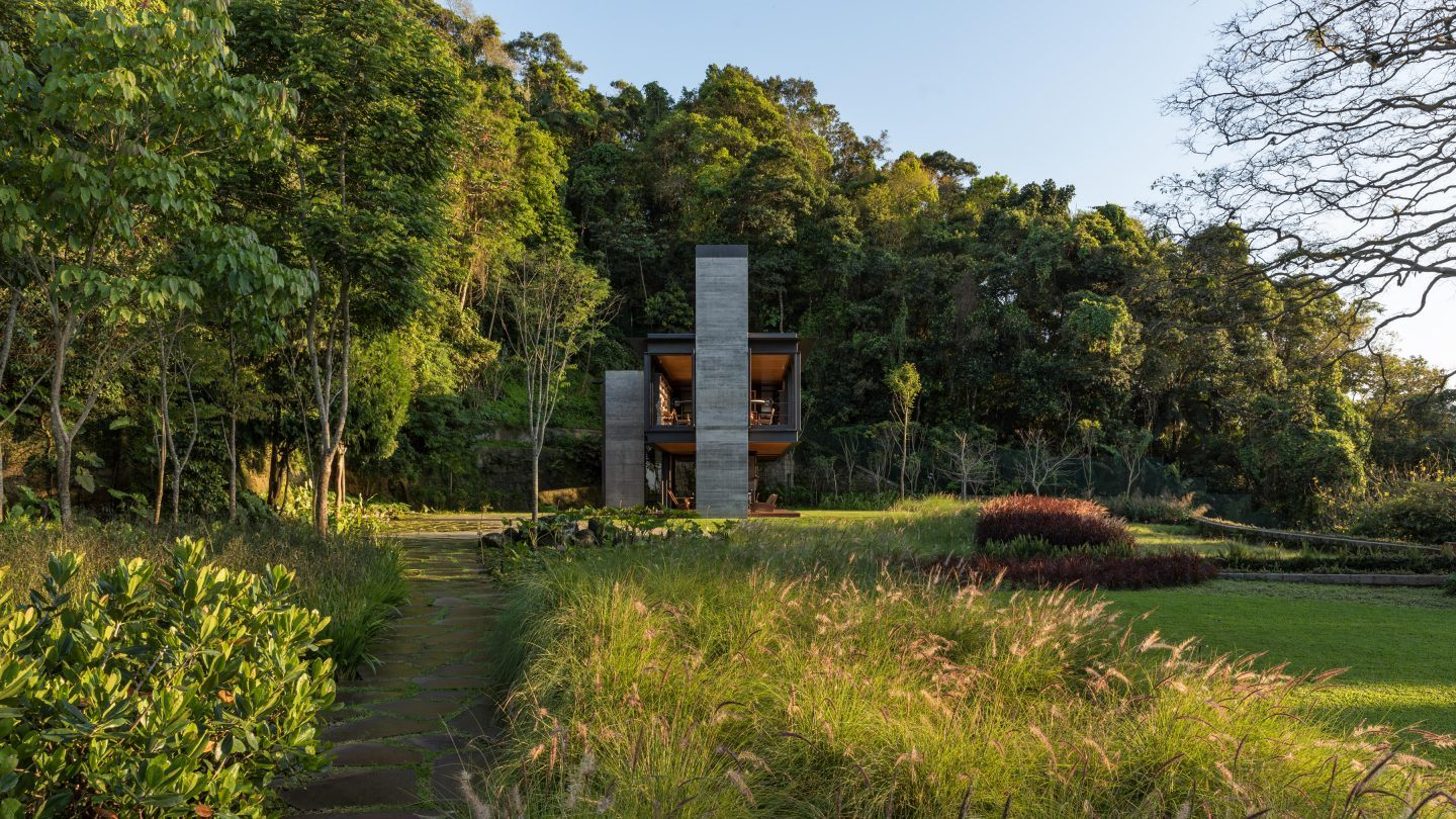 The house is surrounded by lush and vibrant greenery and tropical vegetation on all sides