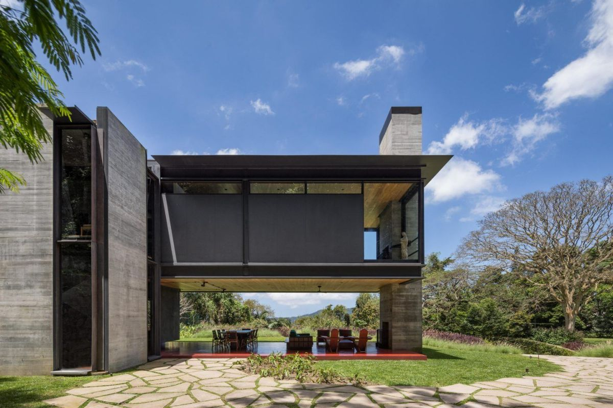 The cantilevered steel and glass volume shelters a beautiful and spacious porch below it with an indoor-outdoor fireplace