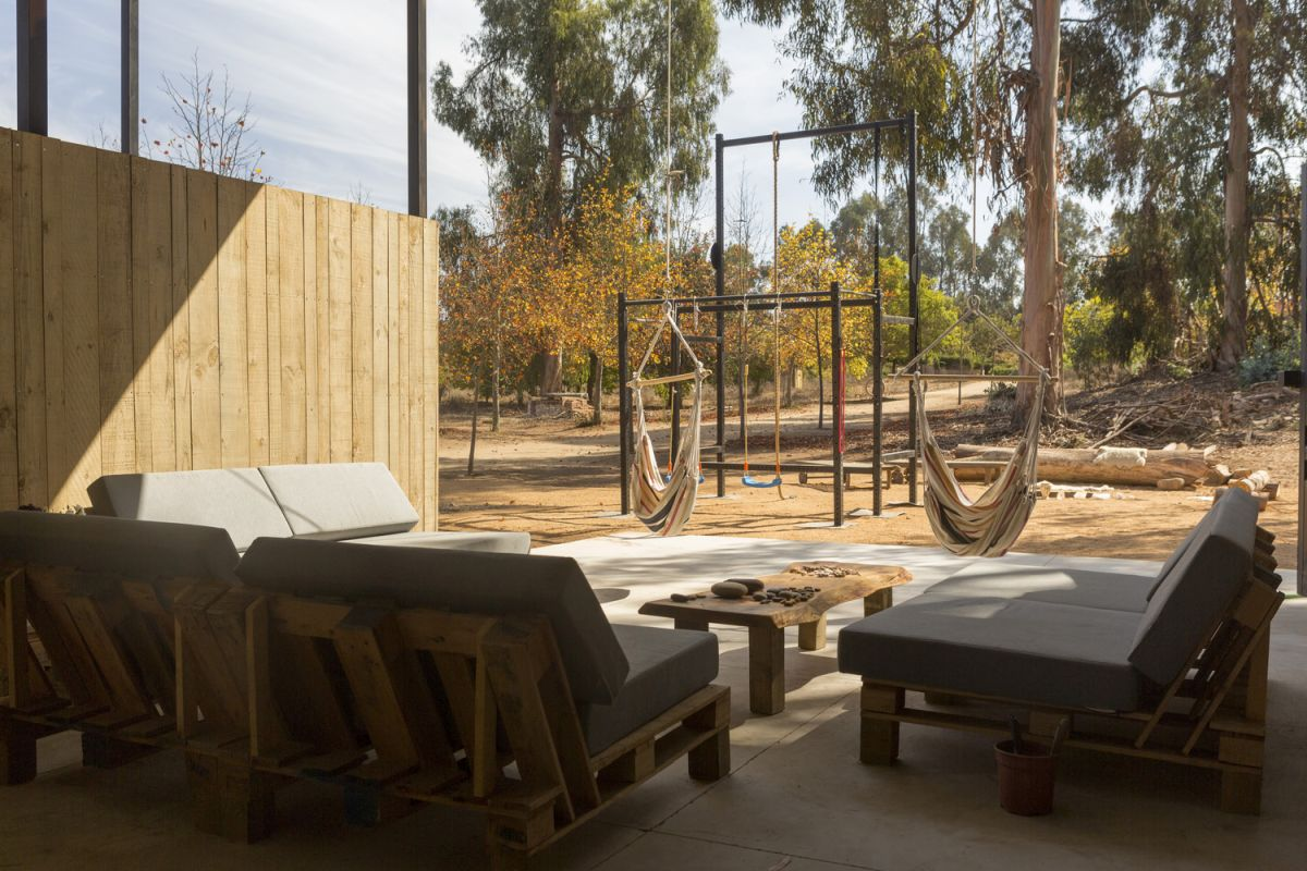 The covered outdoor area is a multifunctional space perfect for lounging and relaxing
